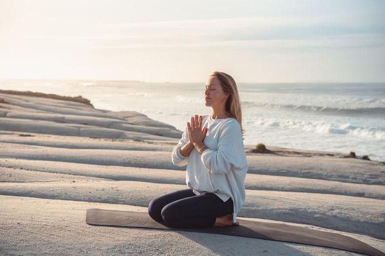 Full length of woman meditating at beach against sea