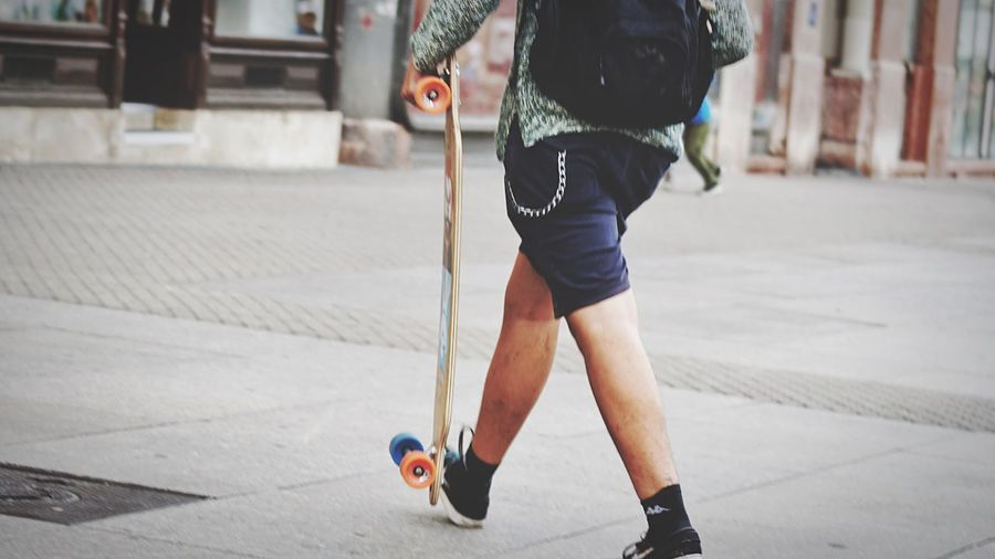 A skater Sport Lifestyles Real People Low Section Leisure Activity One Person Day Sports Equipment Human Leg Body Part Casual Clothing Human Body Part Skill  Skateboard City Footpath Motion Shorts