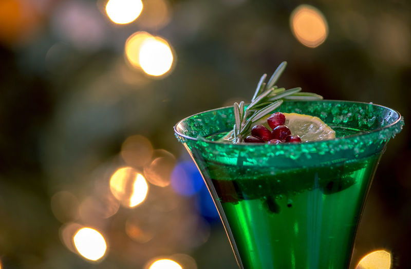 Champagne in  holiday glasses, are garnished with lime, pomegranate seeds and a sprig of rosemary