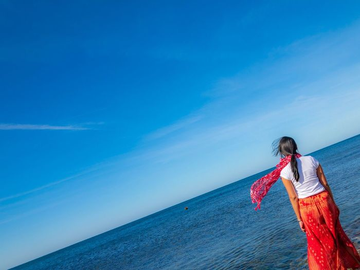Woman standing by sea against blue sky
