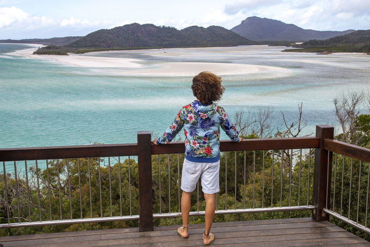 Rear view of boy standing by railing against sea