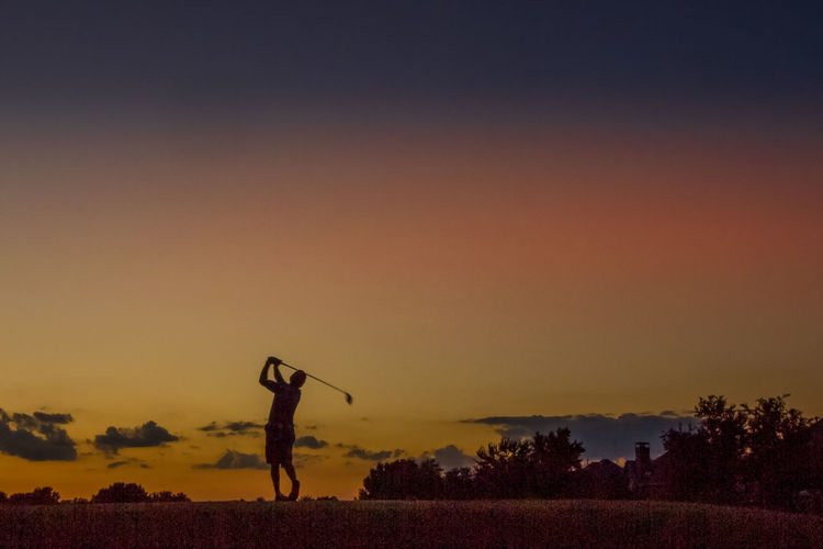 Man Holding Stick On Field Against Sky During Sunset