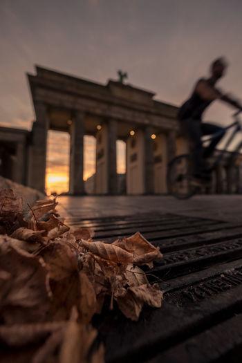 Man riding bicycle by brandenburg gate during sunset