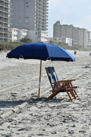Deck Chairs By Umbrella On Sand