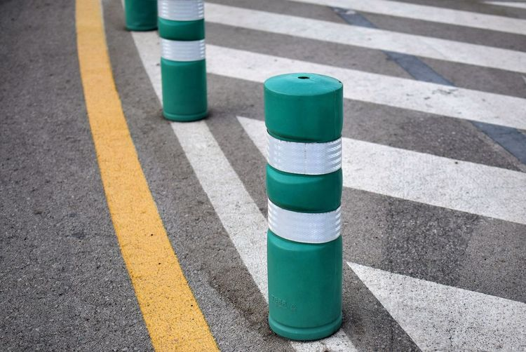 High angle view of green and white bollards on road