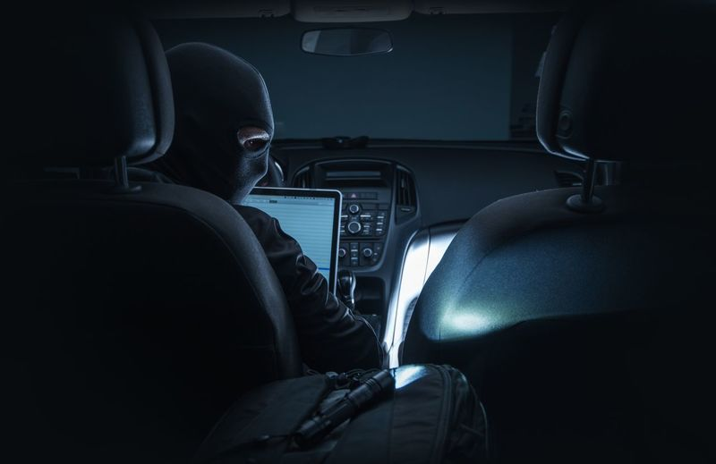 Rear View Of Computer Hacker With Laptop Sitting In Car