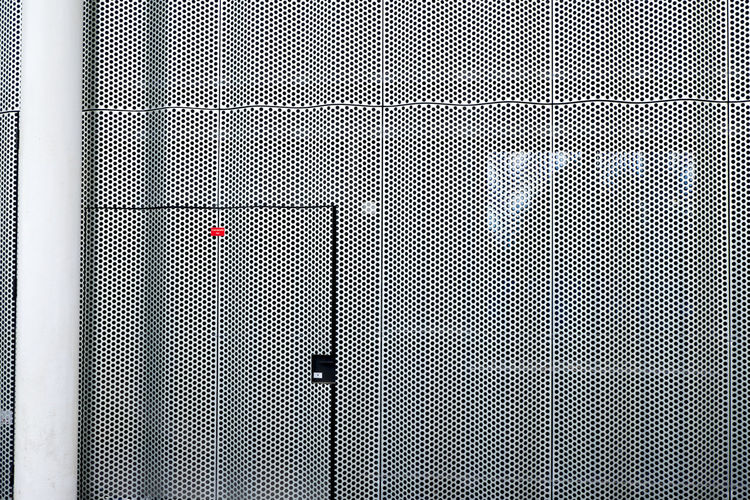 Shadow on metallic door and wall of building