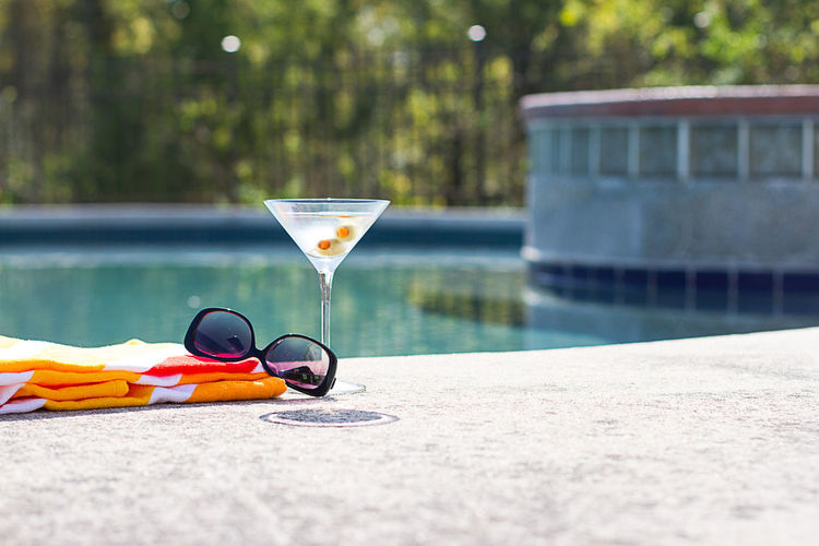 Sunglasses and drink with fabric at poolside