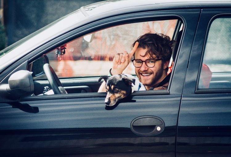 Portrait Of Smiling Young Man With Dog Sitting In Car
