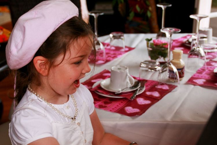 Side view of cheerful girl against elegant dining table