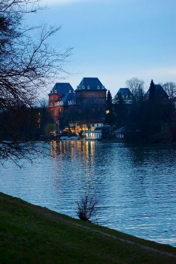 Houses by lake and buildings against sky at dusk
