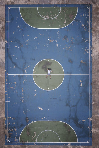 Aerial View Of Man Lying On Basketball Court