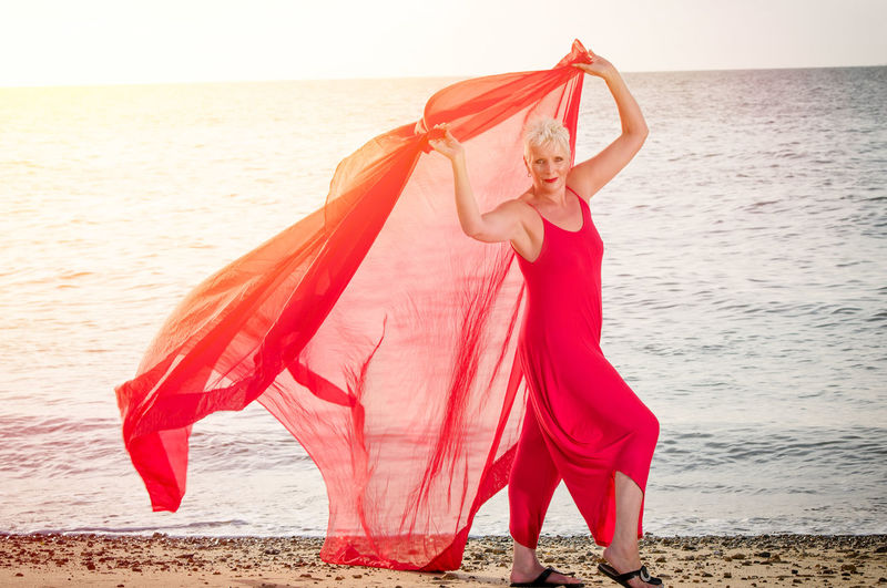 Portrait of smiling woman holding red fabric at beach during sunset