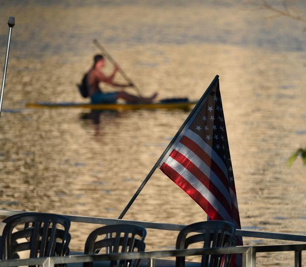 American Flag Against Man Paddleboarding In Lake