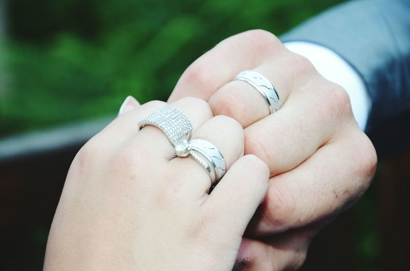 Cropped hands of couple showing engagement rings