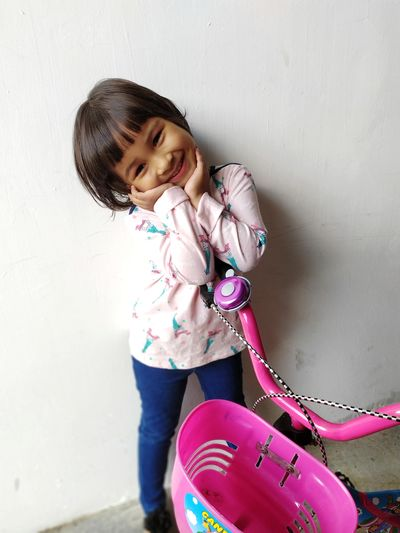 Portrait of cute girl against pink wall