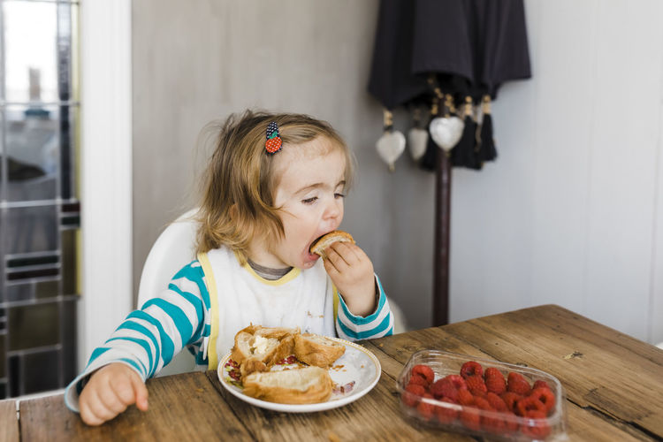 Cute girl eating food on table at home