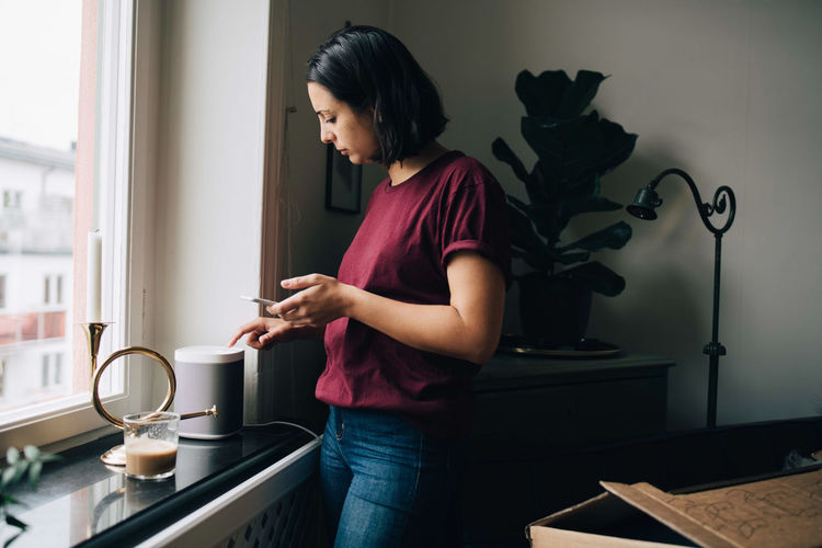 Woman holding mobile phone at home