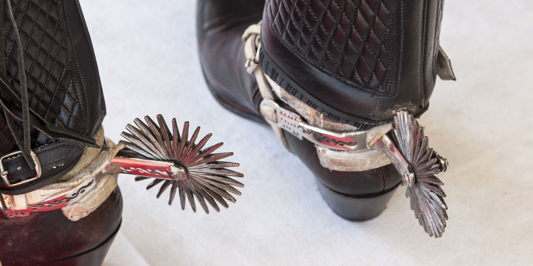 Low section of man wearing shoes with spurs