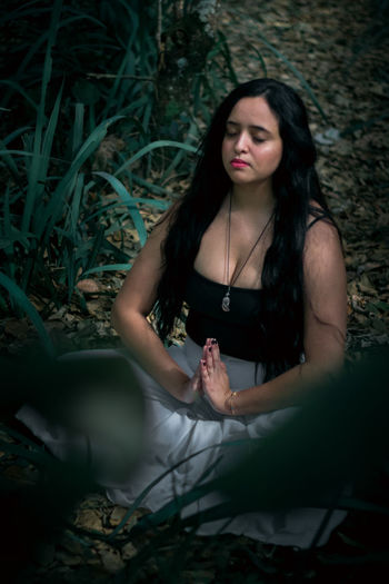 High angle view of woman with eyes closed mediating on land in forest