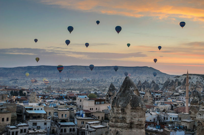 Hot air balloons over town against sky during sunset