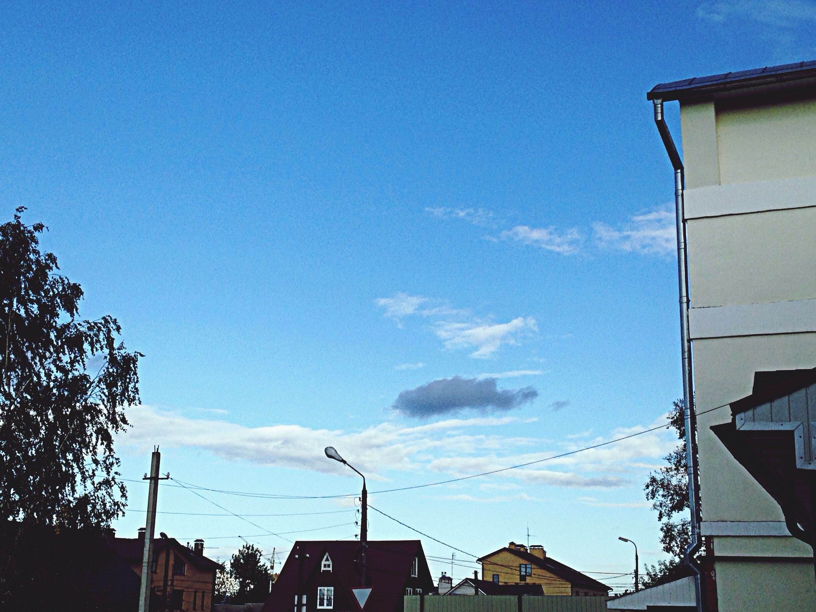 building exterior, architecture, built structure, low angle view, power line, sky, residential structure, residential building, blue, building, house, cable, city, high section, electricity pylon, electricity, outdoors, street light, no people, day