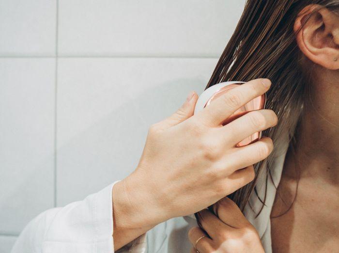 Woman brushing hair in the bathroom