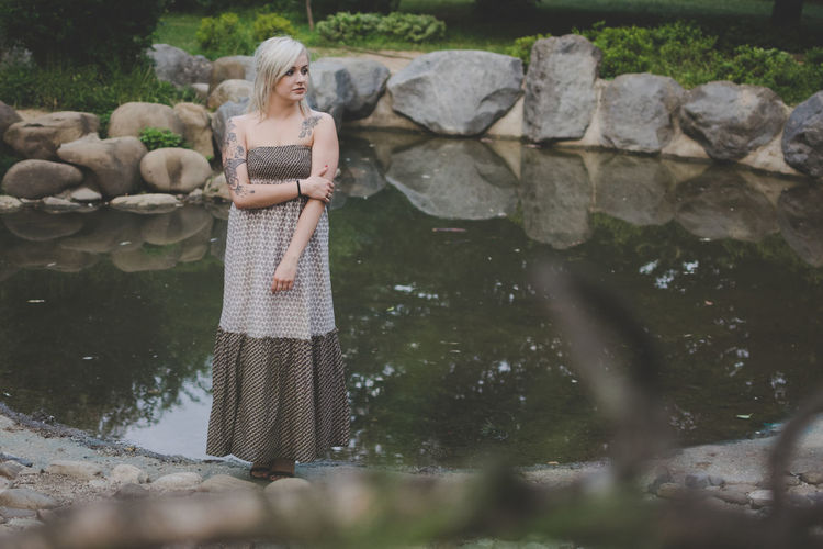 Full Length Of Young Woman In Dress Standing By Pond
