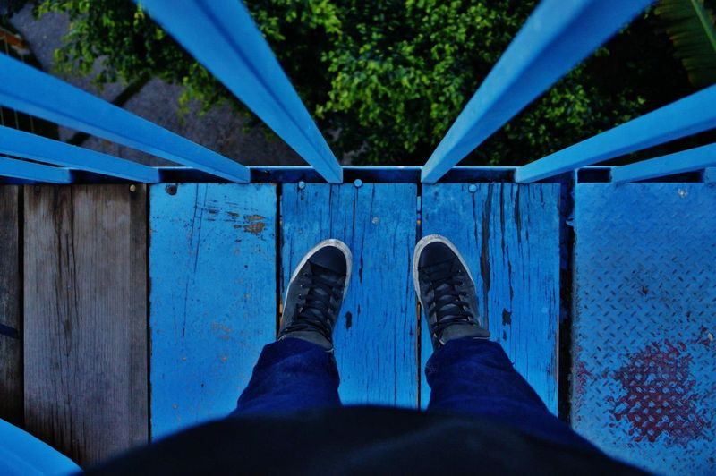 Low section of person standing on footbridge