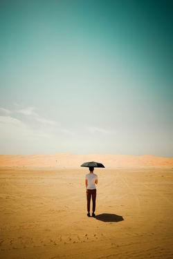 Beauty In Nature Desert Full Length Men Rear View Sand Sky Standing Sunny