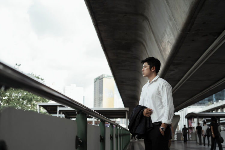 Full length of young man standing on bridge