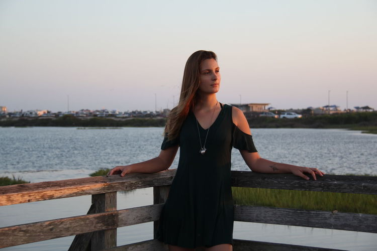 Young woman standing on pier over river at sunset