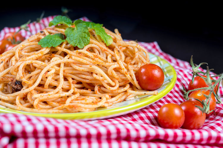 Bolognese in plate by tomatoes on fabric