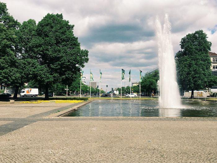 Fountain against cloudy sky