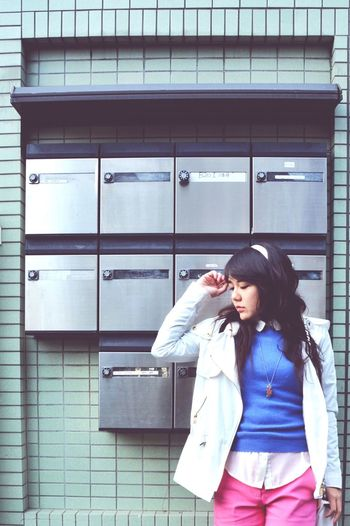 Teenage girl posing against mounted mailboxes