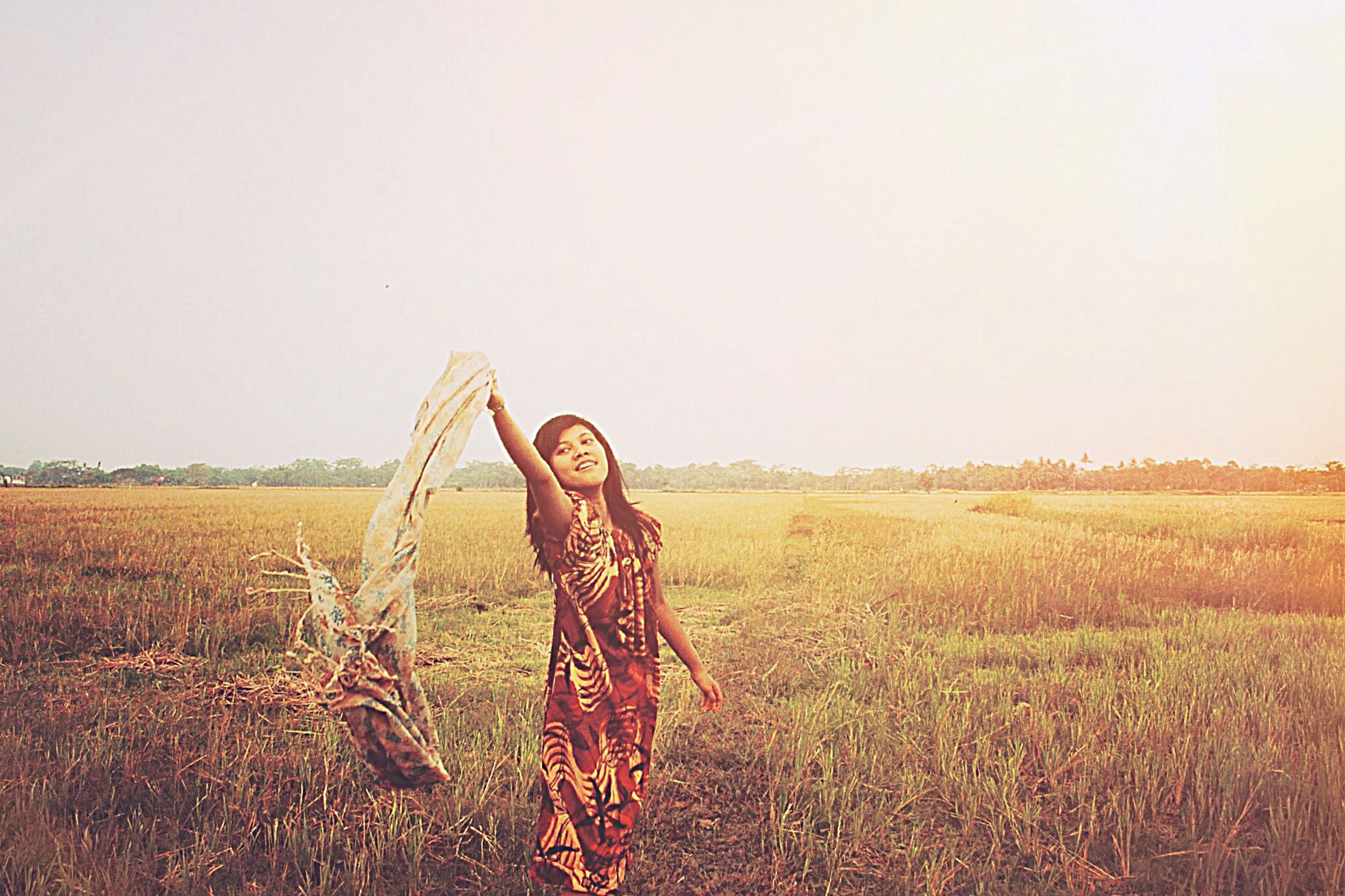 lifestyles, leisure activity, field, grass, casual clothing, clear sky, full length, young adult, standing, person, copy space, landscape, young women, grassy, three quarter length, childhood, sky, elementary age