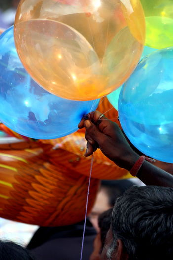 Cropped image of man holding balloons for sale