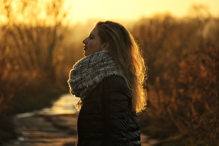 Side view of young woman looking at sunset