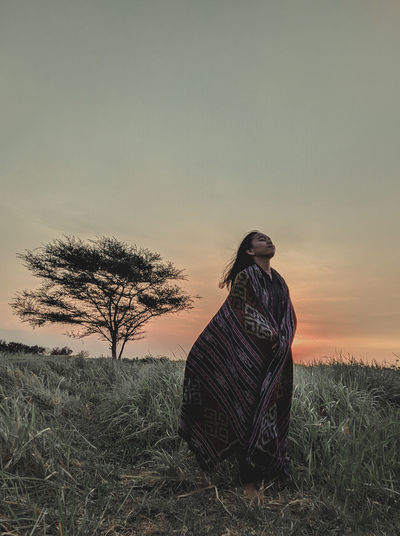 Woman with blanket standing on grassy land against clear sky during sunset