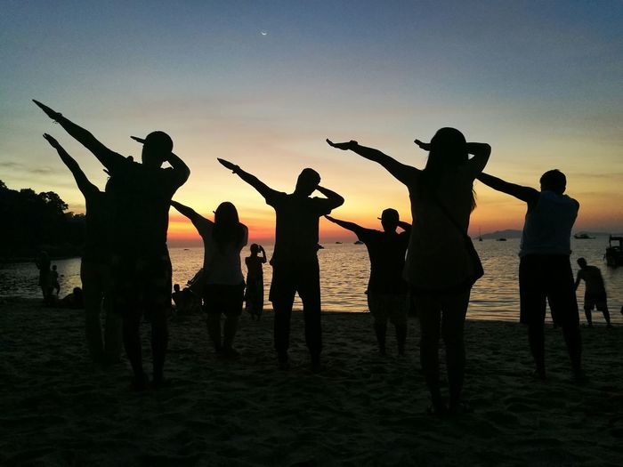 Silhouette People Dabbing On Beach Against Sky During Sunset