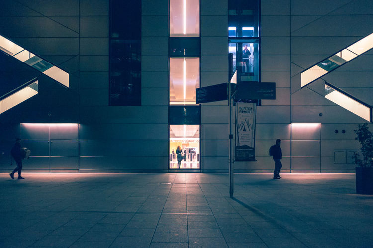 Woman walking in illuminated city at night