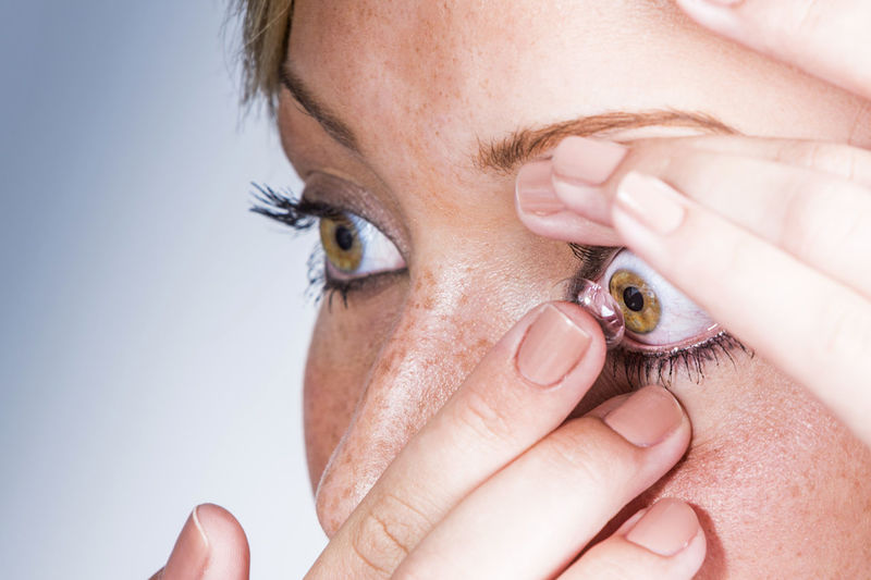 Close-up portrait of a woman putting contact lenses in
