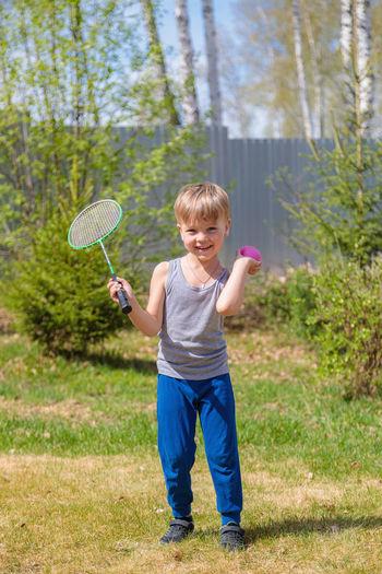 Full length portrait of boy standing in grass