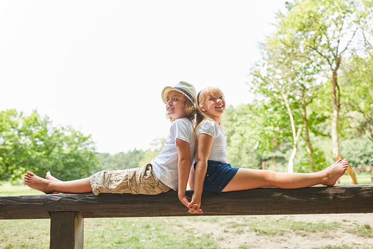 Portrait Of Siblings Sitting On Bench Against Clear Sky At Park