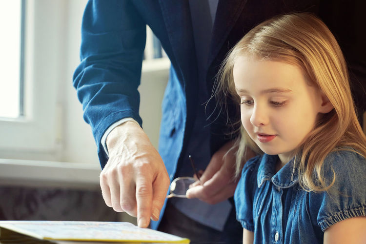 Midsection of father explaining homework to daughter at home