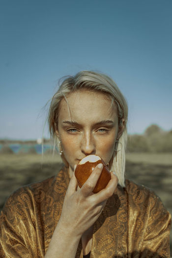 Portrait of woman eating apple against clear sky