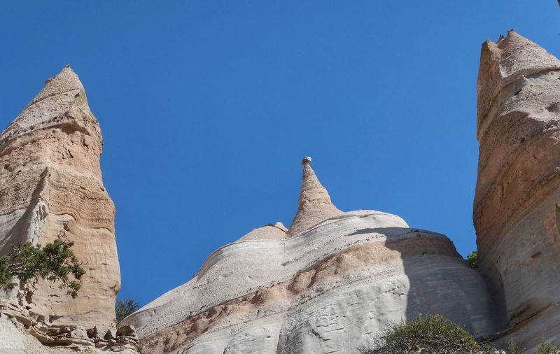 Low angle landscape of triangular rock formations in Kasha-Katuwe Tent Rocks National Monument Tent Rocks Rock Formations New Mexico Kasha-Katuwe Kasha-Katuwe Tent Rocks National Monument EyeEm Selects Low Angle View Blue Sky Nature Day No People Sunlight Clear Sky Travel Destinations History Solid Rock Formation Travel Plant Outdoors Rock