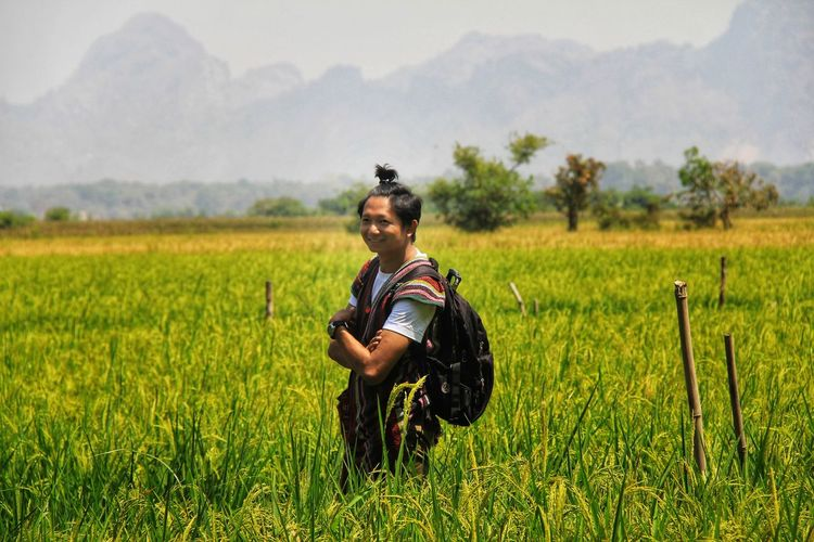 Smiling woman standing on grassy field