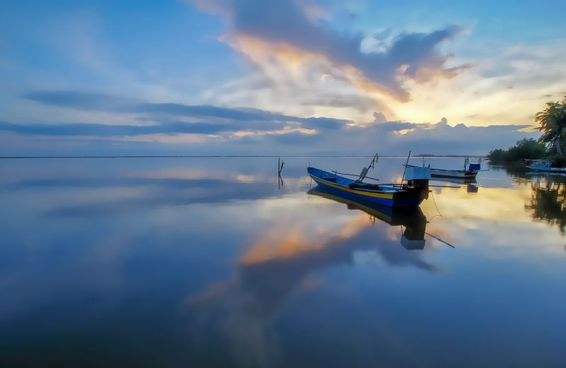 Fishing boat in sea against sky during sunset