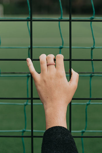 Cropped image of hand holding metal against wall